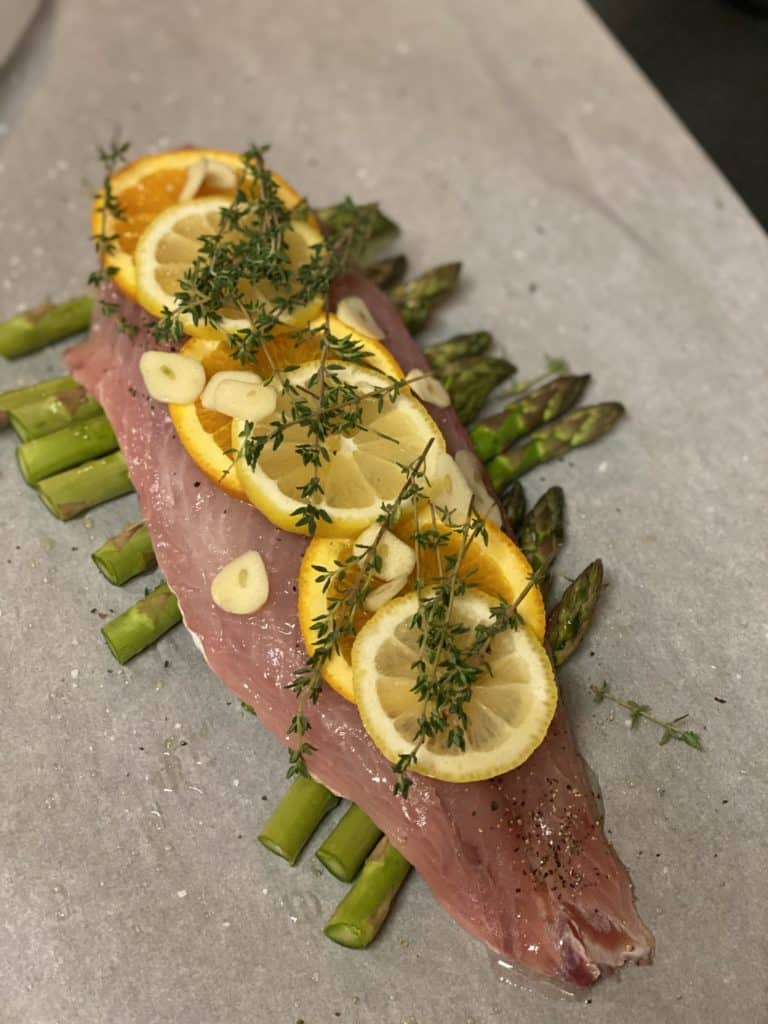 a piece of red snapper with orange and lemon slices, garlic and fresh thyme