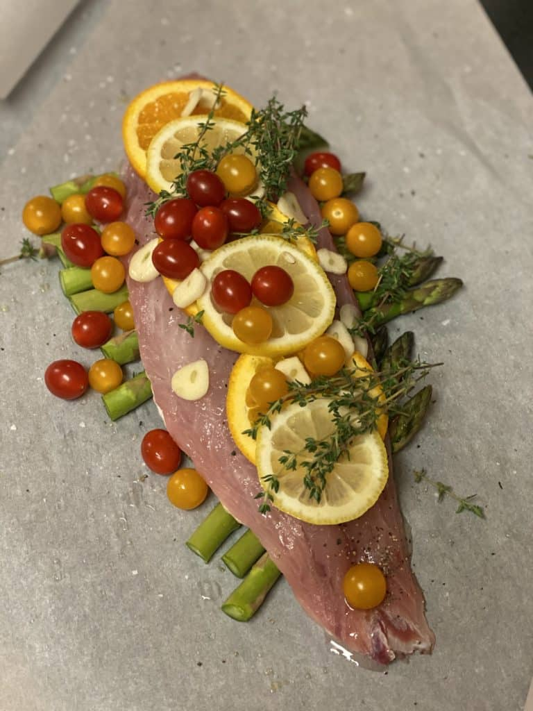a piece of red snapper with lemon and orange slices and cherry tomatoes