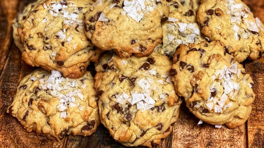 salted chocolate chip cookies displayed on a wooden board