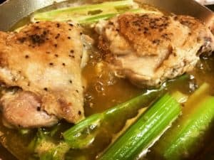 browned turkey thighs simmering in a pot of turkey broth and celery