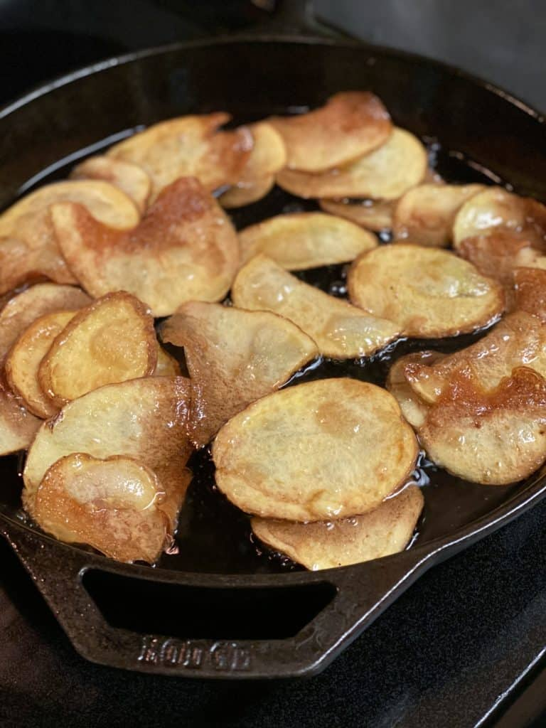 potato chips browning in a cast iron pan