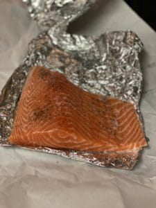 a piece of salmon seasoned with salt and pepper