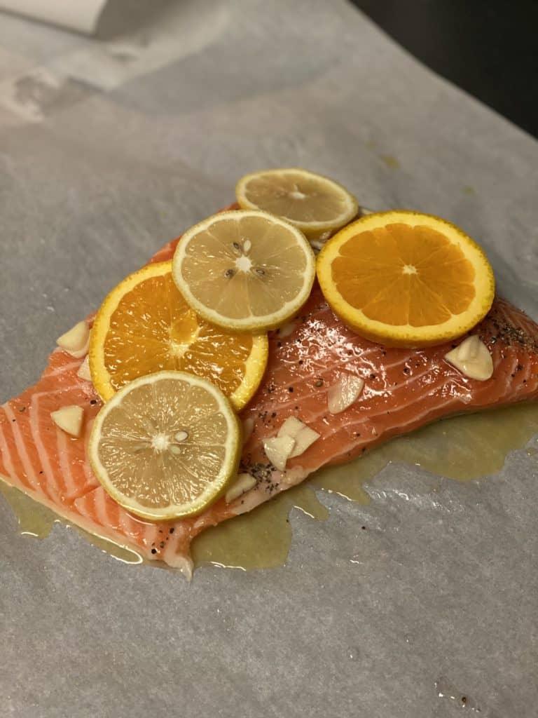 salmon topped with garlic, orange and lemon slices