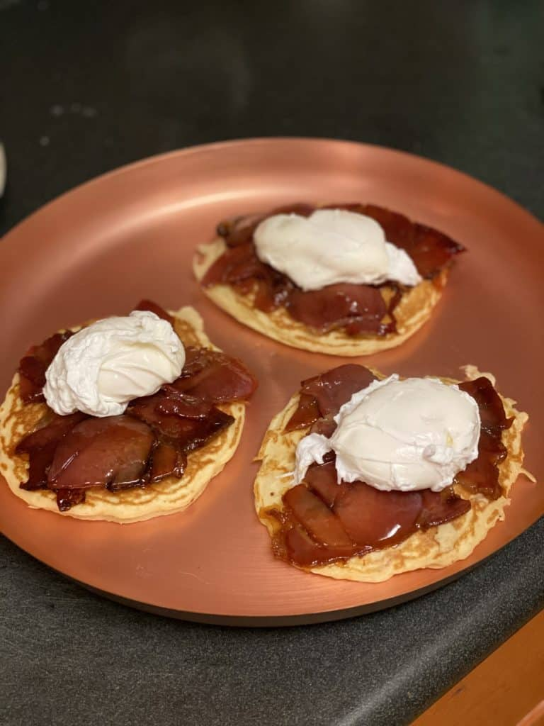 three pancakes topped with candied country ham and poached eggs