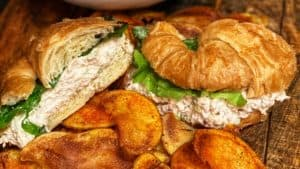 a chicken salad croissant with a side of cajun chips