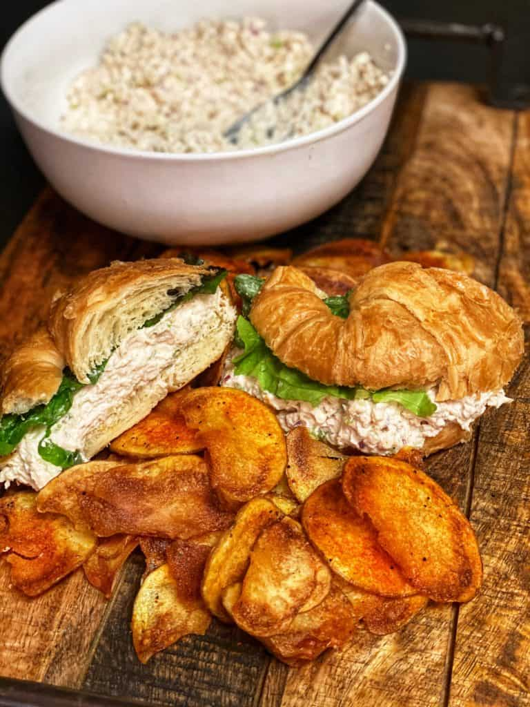 a croissant chicken salad sandwich and homemade cajun potato chips