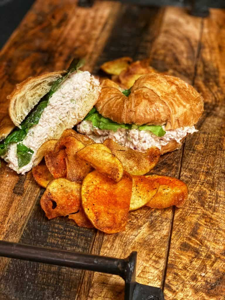 chicken salad croissant with a side of cajun chips