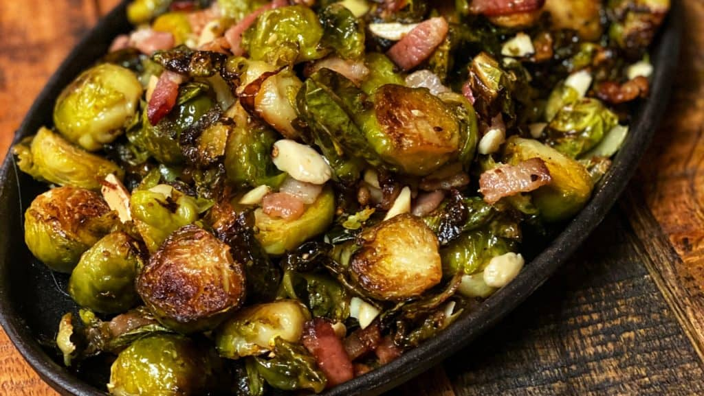 A fajita pan full of roasted Brussels sprouts with bacon and almonds
