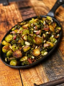 a cast iron pan of roasted Brussels sprouts with bacon and almonds