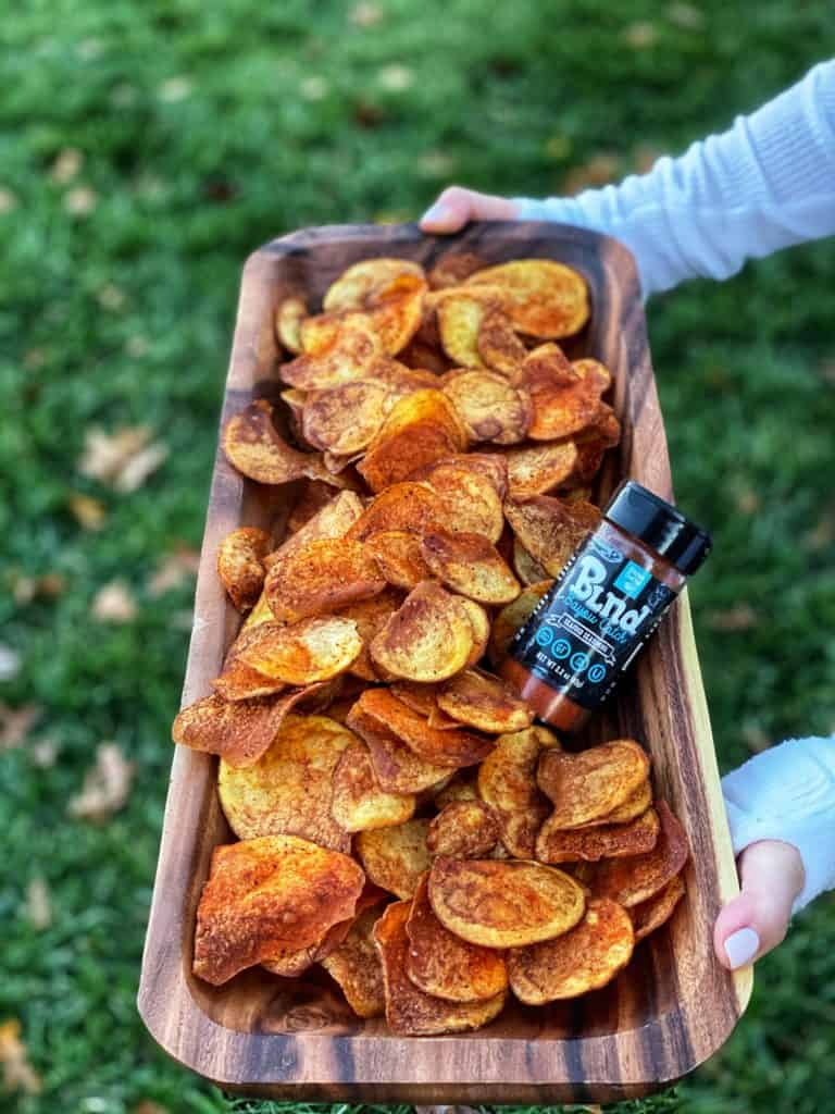 a wooden bowl of homemade cajun potato chips and a jar of kitchen crafted seasoning