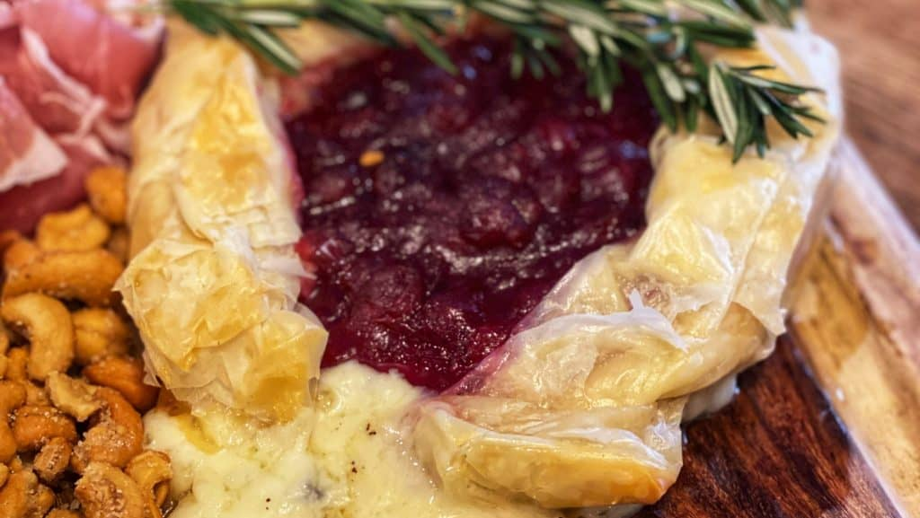 a wheel of baked brie with cranberry jam