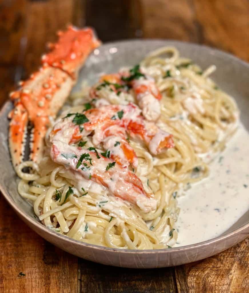 a bowl of crab alfredo pasta