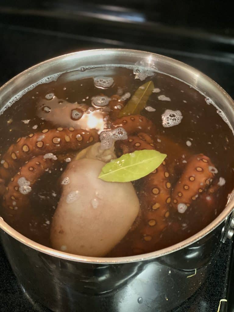 octopus simmering in a pot of water for my grilled octopus salad