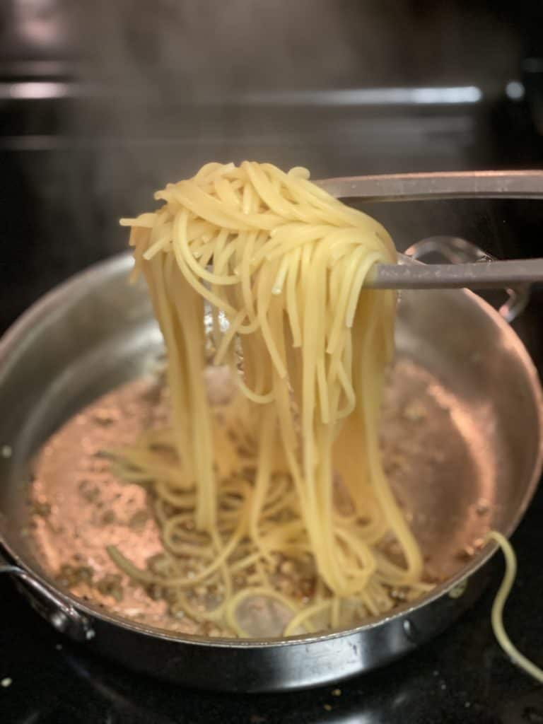 spaghetti going into a pan