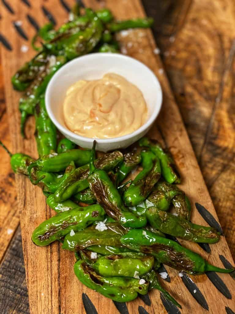 a plate of blistered shishito peppers with Sriracha mayo