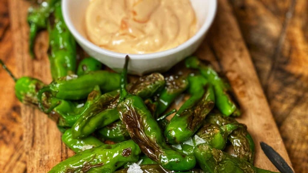 blistered shishito peppers on a wooden board with a side of Sriracha mayo