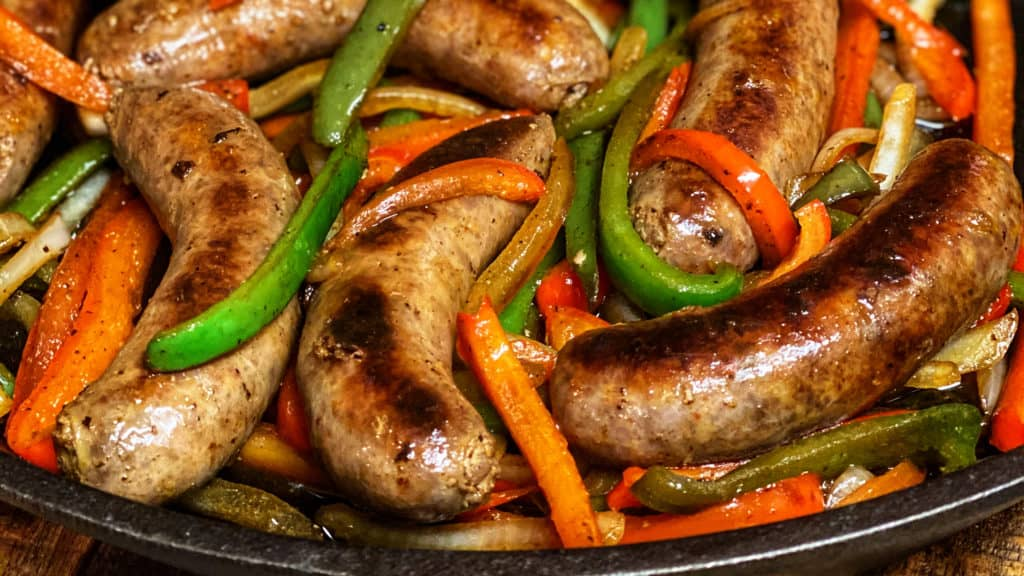 a cast iron pan full of Italian sausage and peppers
