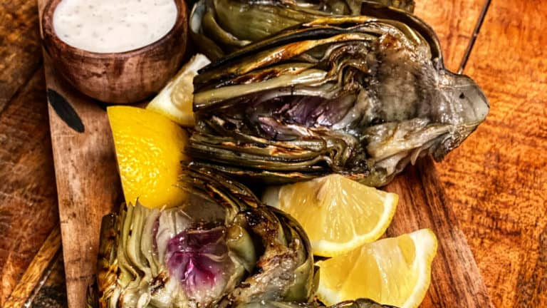 grilled artichokes with lemon on a wooden platter