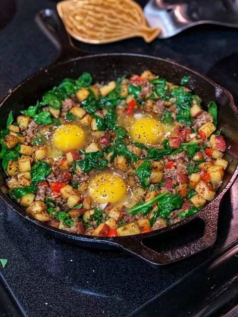 three eggs in a cast iron pan with potatoes and red pepper