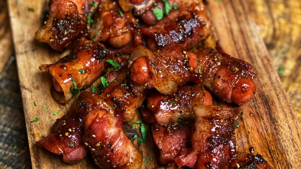 a wooden platter of bacon wrapped smokies