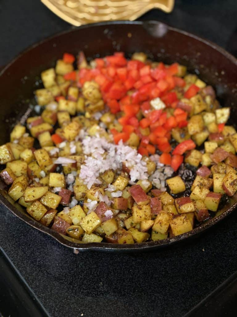 potatoes, shallots and red pepper in a cast iron pan