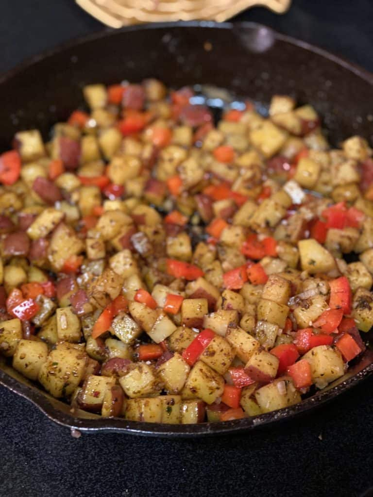 potatoes and red peppers browned in a cast iron pan