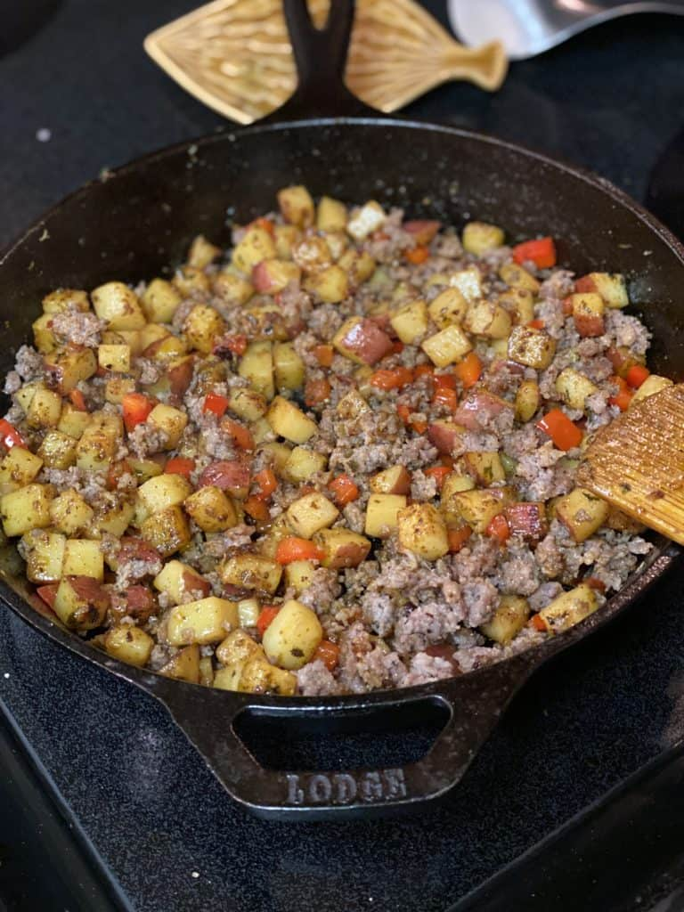 sausage and potatoes in a cast iron pan