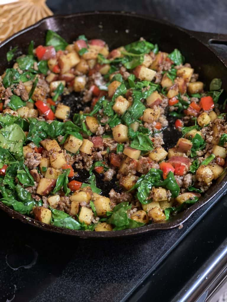 potatoes, sausage and spinach in a cast iron pan for the best breakfast skillet