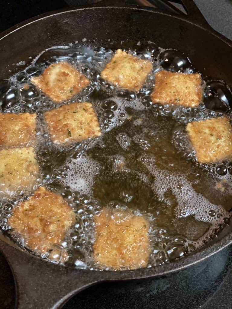 deep fried toasted ravioli frying in a cast iron pan