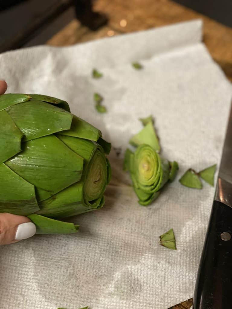 cutting the top of an artichoke off
