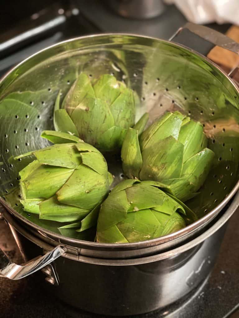 artichoke halves in metal colander