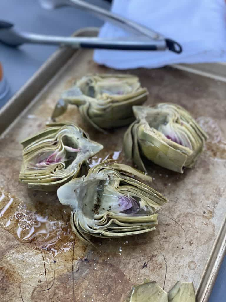 steamed artichokes halves on a pan drizzled with olive oil