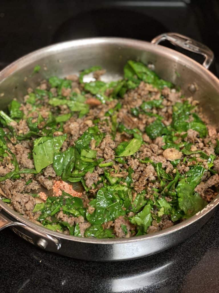 a mixture of sausage and chopped spinach for stuffed portabella mushrooms