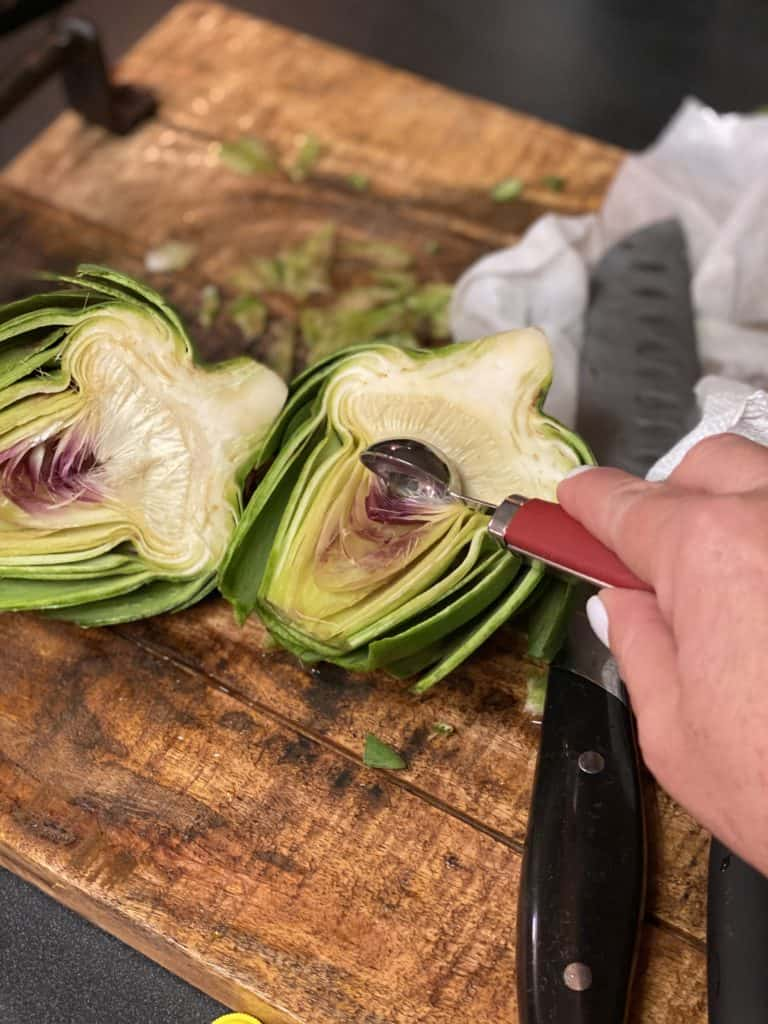 scooping out the furry inside of an artichoke with a melon baller