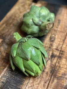 two fresh artichokes on a wooden board for grilled artichokes