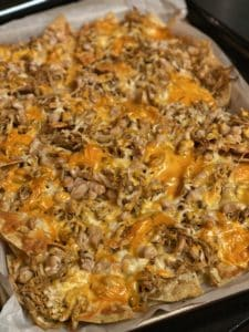 a pan of loaded chicken nachos with melted cheese