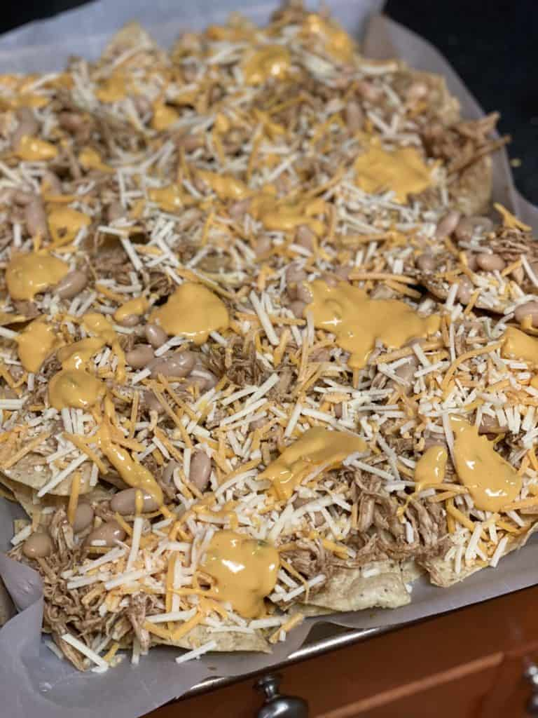 shredded chicken, cheese, and beans on tortilla chips