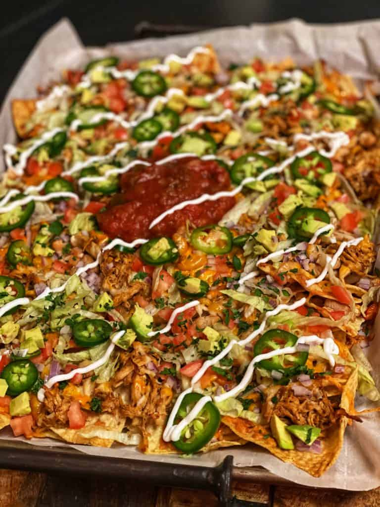 a sheet pan of fully loaded chicken nachos