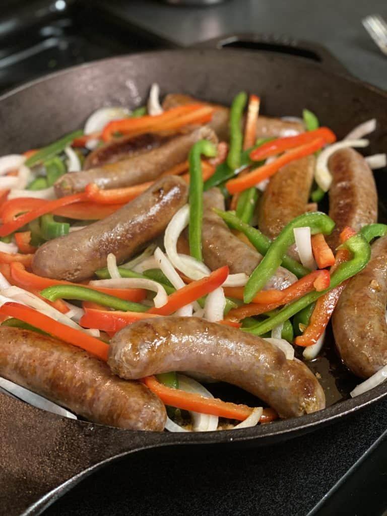 a cast iron pan of sausage and peppers cooking
