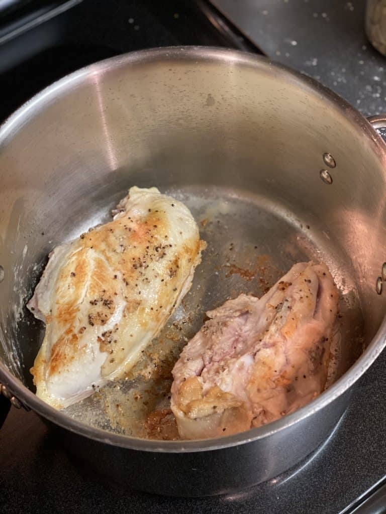chicken breasts browning in a pot