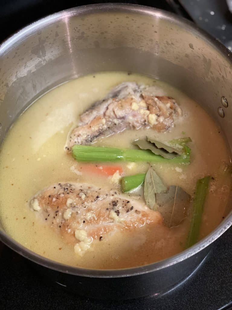 chicken simmering in a pot