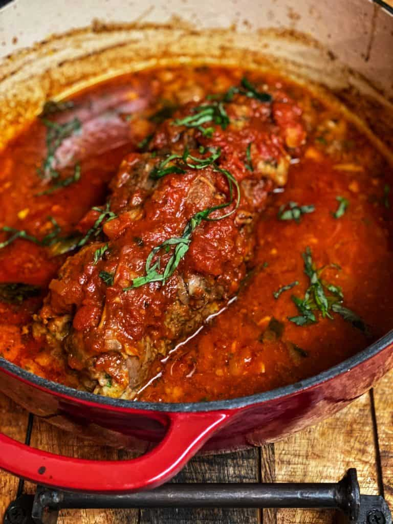 braciole in a red enamel cast iron pan
