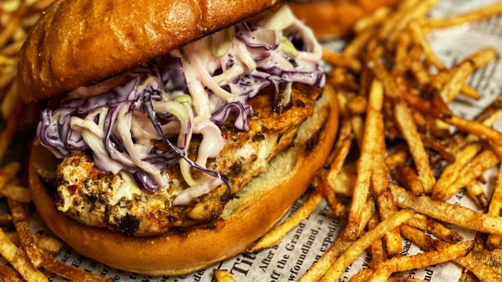 two blackened grouper sandwich with shoestring french fries on newspaper