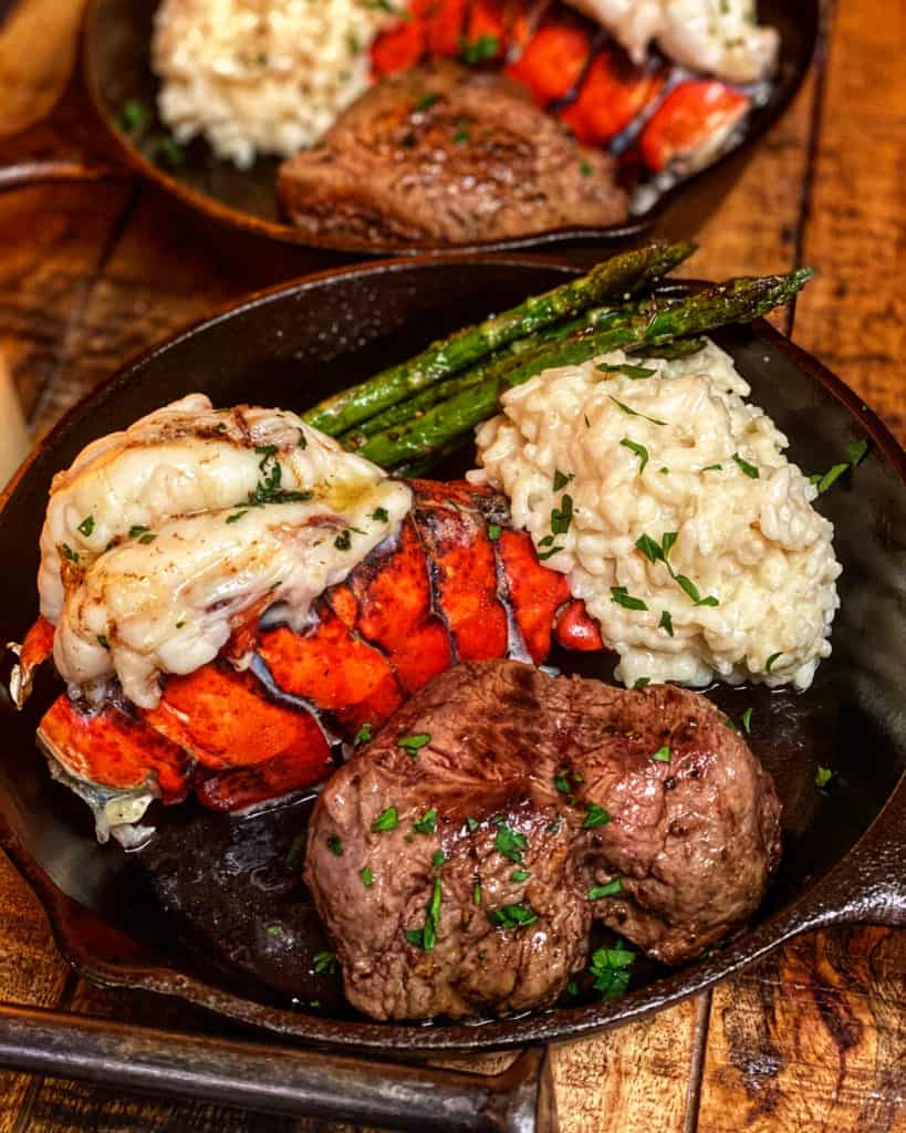 a filet and lobster tail in a cast iron pan