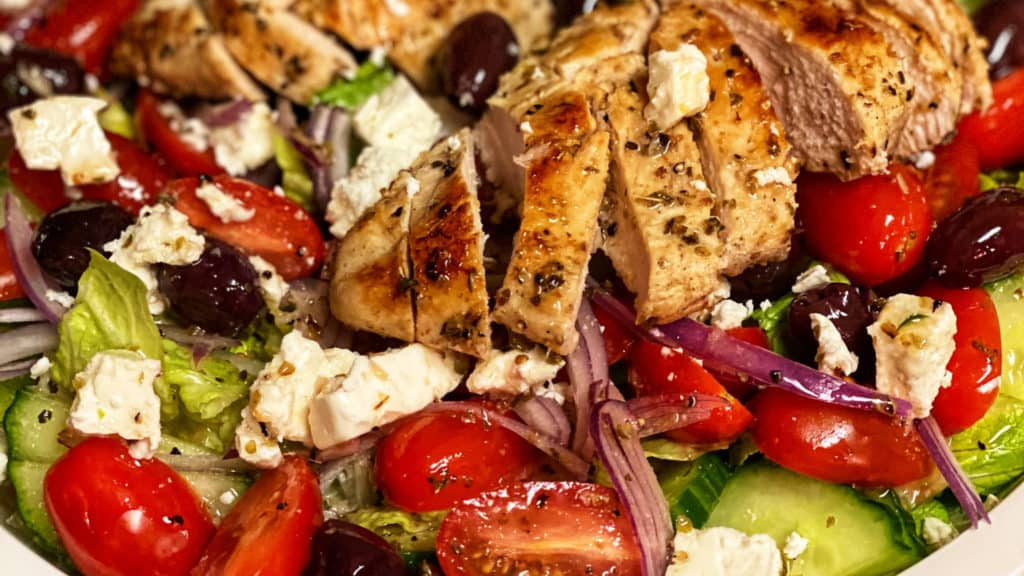a white plate of Greek Salad with two chicken breasts sliced