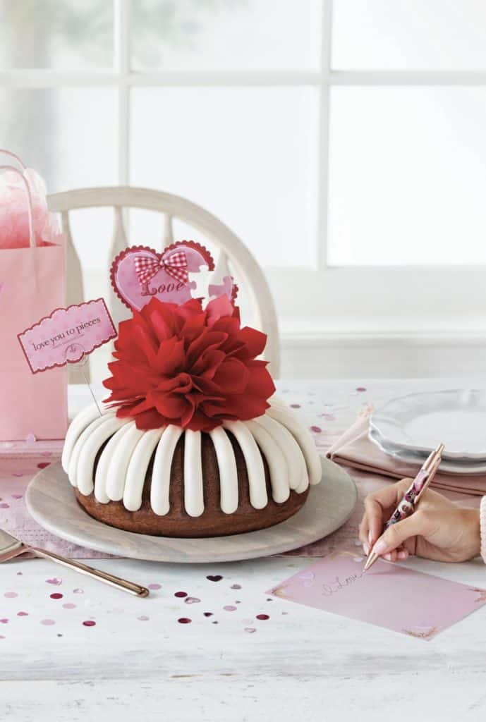 a bundt cake with white drip frosting topped with a red flower for Valentine's Day dinner at home