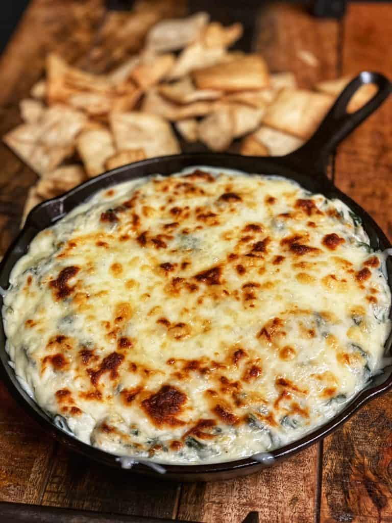 spinach and artichoke dip in a cast iron pan