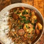 A bowl of The Best New Orleans Style Gumbo in a light grey bowl with rice sitting on a wooden platter
