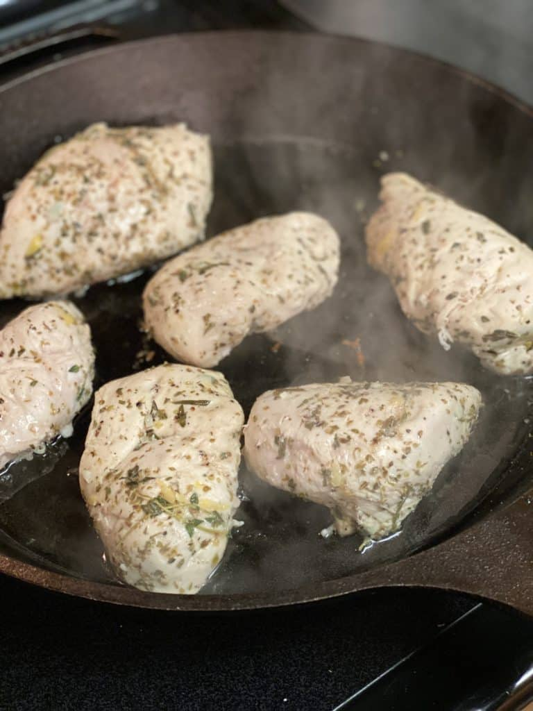 six chicken breasts searing in a cast iron pan