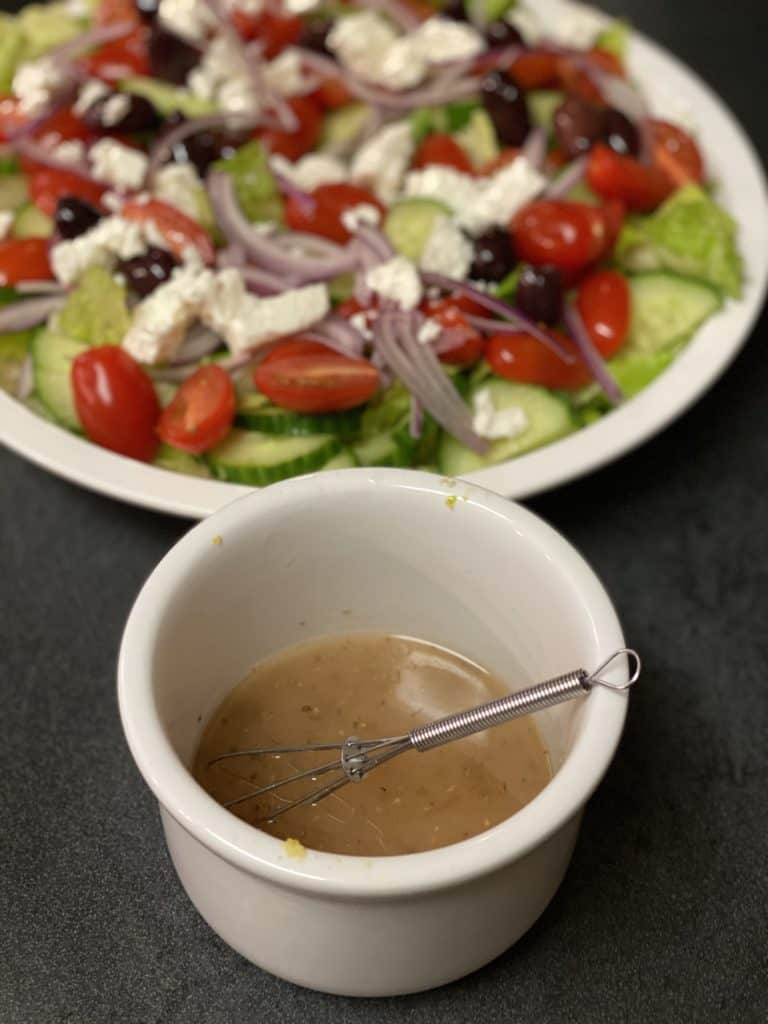 a bowl of Greek salad dressing and a Greek salad with sous vide chicken